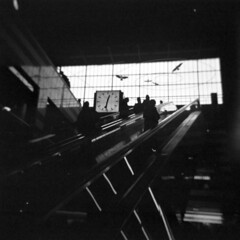 escalator silhouettes (mathias-erhart) Tags: holga person people silhouette silhouettes escalator movingstairway movingstaircase movingstairs clock watch