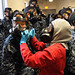 A fire fighting instructor assists a recruit with how to properly seal her gas mask.
