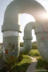 Trail of Pipes (Spike's Shoes) Tags: pictures street city autumn color colour green art industry grass vertical wall illustration painting way outside photography graffiti daylight mural europe industrial european graphic artistic loop photos outdoor drawing district curves steve stock pipes central cities cityscapes poland polska polish arches images east trail photographs snapshots daytime passage curved eastern picturesque looping contrasts heating ducts imagery lodz skjold juxtapositions pl05 balucki centralpoland hotwaterducts