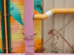 Intruding on the Real World (mikecogh) Tags: bowden publicart pipe drain color colour comparison weeds intrusion pipes parallel fence change painted abstract