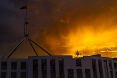 sunset drama (nzfisher) Tags: storm stormy sunset dusk twilight sundown 50mm canon orange parliament canberra act australia flag sky clouds building architecture