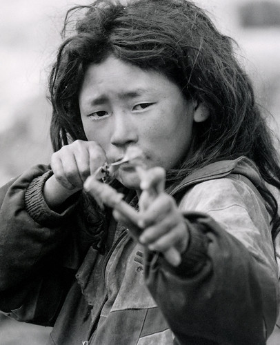 tibetan boy aiming at the camera with a slingshot
