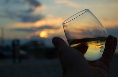 Fotografía de una copa sujeta con la mano izquierda en cuyo contenido se refleja una preciosa puesta de Sol