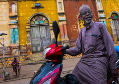 Benin, West Africa, Porto-Novo, old muslim man on a scooter in front of the multicoloured great mosque (Eric Lafforgue) Tags: africa old travel color building heritage tourism church horizontal architecture religious outdoors worship adult muslim islam faith religion colonial afrobrazilian mosque transportation bahia westafrica historical benin portuguese 2people twopeople adultsonly islamic portonovo colourimage brazilianstyle     adjac hogbonou benin00285