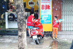 In their own world (Roving I) Tags: boys playing guns lego motorscooters trees signs shops retail puddles weather imaginaton street danang vietnam