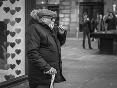 Heart Breaking (Leanne Boulton) Tags: monochrome people portrait profile urban street candid portraiture streetphotography candidstreetphotography candidportrait streetlife sociallandscape man male old age aged elderly face facial expression wrinkles emotion feeling smoke smoker smoking cigarette cap walkingsticks window display juxtaposition storytelling tone texture detail depthoffield bokeh naturallight outdoor light shade city scene human life living humanity society culture canon5d 5dmarkiii 70mm canon character ef2470mmf28liiusm black white blackwhite bw mono blackandwhite glasgow scotland uk
