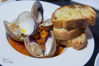 Clams immersed with guanciale in a rich tomato sauce.