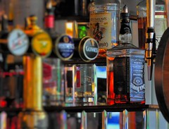 Spotted And Cropped From Sixty Yards (standhisround) Tags: beer bar reflections focus colours bottles drink whiskey blurred pump liquor rum jackdaniels captainmorgan optics liquer