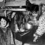 Inuit woman tending the qulliq (seal-oil lamp) inside an igloo, Nunavut / Une femme inuite s'occupe d'un qulliq (lampe alimentée à l'huile de phoque) dans un igloo, au Nunavut thumbnail