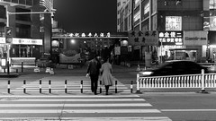 Night 36/52 (Go-tea 郭天) Tags: street urban city outside outdoor people bw bnw black white blackwhite blackandwhite monochrome asia asian china chinese shandong canon eos 100d 24mm prime night huangdao qingdao pedestrian man woman couple husband wife crossing cross road lines car light fences buildings downtown risk risky careful carefully movement speed fast danger dangerous glasses moving coats winter cold protect protected protection 52 52project 36 dark love warning attention