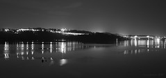 a faint insular vision through night and fog (lunaryuna) Tags: uk wales bangor menaistrait anglesey menaibridge shoreline seastrait night nightlights nightvision nocturnalphotography nightphotography water reflections distortions coast blackwhite bw monochrome panoramicviews seeingdouble fog weathermood lunaryuna