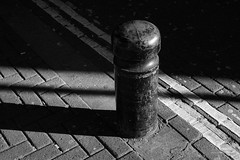 Bollard in Sunlight (cybertect) Tags: canonfd55mmf12aspherical london londonwc2 phoenixstreet sonya7 wc2 blackwhite blackandwhite bollard doubleyellowline monochrome shadow sunlight yellowline