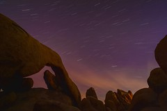15 minute time exposure at Arch Rock, White Tank campground, Joshua Tree. (eikonologos.images) Tags: stars evening nationalpark twilight joshuatree geology whitetank startrail archrock