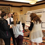 Students listening to another student's research presentation