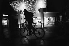 6/365 Hold On Tiger (denise.ferley) Tags: norwich night nighttime dark bw blackandwhitephotography bicycle city citylife peoplewatching people streetphotography street sonynex5 shopping shoppers cycle tiger watching england 3662016 366 uk urban