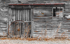 Leaning On A Barn Door (John Kocijanski) Tags: barn wheel wall door rustic selectivecolor wood building canon85mmf18usmlens hss rust
