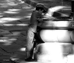 Neno entre luces e sombras. Child between lights and shadows. (Esetoscano) Tags: neno niño child luces lights sombras shadows sol sun fuente fountain agua water pavimento pavement bw bn byn cidadevella oldtown acoruña galiza galicia españa spain