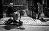 going and coming (Chilanga Cement) Tags: fuji fujix100f xseries x100f street streetphotography bw blackandwhite people beinghuman advancing wheel wheels wheelchair age wisdom shopping westlancashire ormskirk