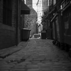 Alley light (Gabo Barreto) Tags: leeds yorkshire england alley cobbles rubbishbins film fujiacros fuji kiev88 commiecamera sovietcamera russiancamera 120 mediumformat 6x6 blackandwhite monochrome selfdeveloped scannedfromfilm