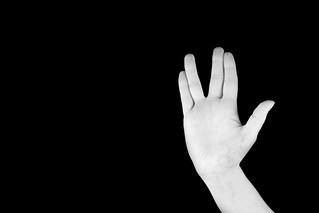 Woman' hand on black background showing open palm with gesture of long life and prosperity