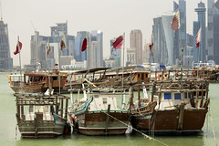 Qatar flags  in Doha Bay (Paul Cowan) Tags: doha qatar dhow sea towers cloudy emir tamim loyalty pictures boat ship ferry siege crisis arab gulf arabiangulf persiangulf vertical logo middleeast flag 2018 city capital skyline arabian arabia architecture bay modern corniche building sky water blue skyscraper reflection travel tower landmark qatari culture downtown harbor harbour development highrise skyscrapers bank coastline wealth anchored dohabay postmodern nikkor 13528 nikkor135f28