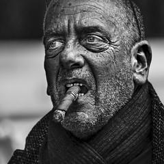 Man smoking a cigar (Ales Dusa) Tags: man cigar bw blackandwhite face outdoor cigarsmoker smoker alesdusa streetportrait closeup dof fullframe canoneos5dmii person people human humanity strongcontrast streetshot winstonchurchillimpersonation shortbeard scarf monochrome