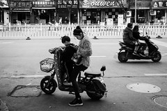 Don't text and drive (Go-tea 郭天) Tags: hangzhou linan text mobile phone cellular cell cellphone connected connexion data network texting mother son kid child boy woman young busy motorbike motorcycle parked movement speed road family 2 together parking basket street urban city outside outdoor people candid bw bnw black white blackwhite blackandwhite monochrome naturallight natural light asia asian china chinese canon eos 100d 24mm prime