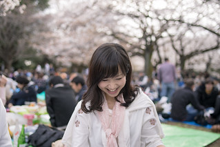 Young woman enjoying hanami party under cherry trees