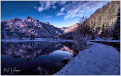 Almsee Mondlicht III by Karl Glinsner - Winterlicher Mondaufgang am Almsee nahe Grünau. Im Hintergrund die Gipfel des Toten Gebirges .Der Almsee ist ein kleiner See mit einer Länge von 2,3 km im Salzkammergut. Er liegt ca. 11 km südlich von Grünau im Almtal am Nordrand des Toten Gebirges. Das Gebiet um den Almsee steht seit 1965 unter Naturschutz.  Wintry moonrise at the Almsee near Grünau. In the background the peaks of the Totes Gebirge(mountains). The Almsee is a small lake with a length of 2.3 km in the Salzkammergut. It is located 11 km south of Grünau at the northern end of the Totes Gebirge. Since 1965, the area around the Almsee is under nature conservation