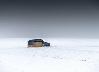 Black barn in a field of snow