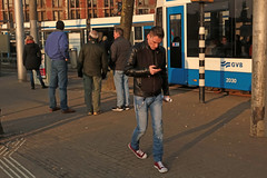 Stationsplein - Amsterdam (Netherlands) (Meteorry) Tags: europe nederland netherlands holland paysbas noordholland amsterdam amsterdampeople candid centrum centre center stationsplein centraalstation station tram transport gvb siemens combino gvb2030 man homme male guy jeans afternoon aprèsmidi people sneakers trainers baskets skets converse allstars chucktaylor chucks smartphone cellphone february 2018 meteorry