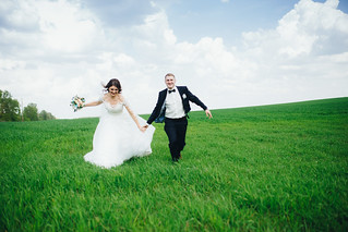 Happy wedding couple running in the field
