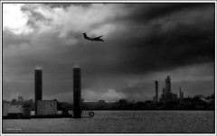 Final approach mono (agphoto100) Tags: plane fokker prop wind clouds rain water river fujifilm s602z piles factory plant waves black white brisbane queensland bw sky landscape