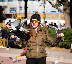 Lady of the birds (Pablo Arrigoni) Tags: birds pajaro pajaros dove paloma palomas outside outdoor square plaza sol sunny city ciudad barcelona españa europa europe girl chica woman women mujer glasses lentes anteojos trip tour canon eos eos70d 18135 70d autumn cap gorro lana viaje vacaciones hollidays color colores colors colours reflect reflejo catalunya catalan