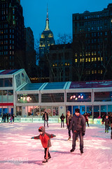 Skaters, New York City  (75374) (John Bald) Tags: bankofamerica bryantpark empirestatebuilding manhattan nyc newyorkcity childskating cold dusk icerink ny skating skatingpavillion snackbar snow twilight winter