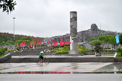 A woman's lot (Roving I) Tags: conicalhats bicycles cycling rainwear roads weather banners sculpture monuments memorials mothers war tamky vietnam