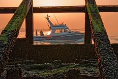 Early Start (Geoff Henson) Tags: dawn sunrise anglers boat daybreak tide barrier wood seaweed sea ocean water glow amber