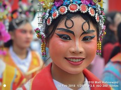2018-02a Bangkok Chinatown (54) (Matt Hahnewald) Tags: matthahnewaldphotography facingtheworld aesthetic springfestival chinesenewyear parade performer dancer makeup lunaryear festival head face painted eyes costume consent fun entertainment travel tourism culture tradition enjoyment socialevent diversity impact traditional cultural folklore touristattraction celebration historical yaowarat bangkok chinatown thailand thaichinese asia photo physiognomy nikond3100 primelens 50mm 4x3 horizontal street portrait closeup outdoor color colorful iconic awesome incredible authentic sightseeing partying photography ambiguity attire oneperson eyemakeup teeth smiling lips headgear headshot lifestyle posingcamera lookingcamera