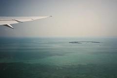 Between you & me (isadora.jpg) Tags: 35mm film point shoot kodak gold 200 yashica t4 aerial ocean sea water green plane window wing qatar banana island flight doha persian gulf
