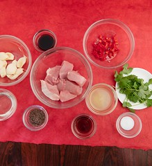 Mise en place marinade and raw pork meat. (annick vanderschelden) Tags: cookingoil oil glass garlic sugar brownsugar fishsauce fish sauce cilantro soysauce salt chili lemonjuice juice redsurface ingredient food preparation belgium