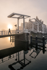 Walk the light (reinaroundtheglobe) Tags: haarlem nederland holland brug gravestenenbrug zonsopkomst mist fog 1person water reflection waterreflections silhouette residentialbuilding residentialarea canal canalhouses sunrise