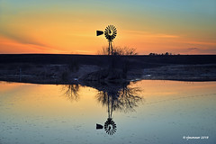 Concert of Color_187033 (rjmonner) Tags: windmillwednesday windmill rural pond country sunset sky reflection farming farm field water blue orange blades reflect tree clouds spring trees iowa midwest cornbelt agronomy agronomic roadside twilight dusk