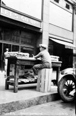 Boy working at newsstand, 1926 (Seattle Municipal Archives) Tags: seattlemunicipalarchives seattle newsstands newsboys downtownseattle 1920s