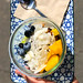 Tasty fruit salad: mango, blueberries, coconut flakes and granola