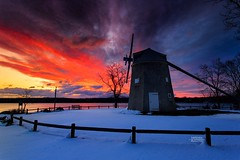 Crushing Winter Sunrise (Dapixara) Tags: canon newengland nature coastal landscape snow trees sky orleans photography windmill winter crushing snowy sunrise capecod massachusetts outdoors travel red clouds dramatic