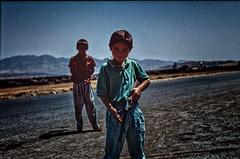 Kid playing soldier in a country where war is real (rvjak) Tags: irak kurdistan iraq children boys enfants garçon soldat soldier jouer play f3 nikon road landscape route paysage argentique film pellicule sky kurdish kurde