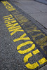 Courtesy on the street (James_D_Images) Tags: sign street entrance exit welcome thank you stencil yellow letters paint faded asphalt concrete pavement angle vertical cracks graphic perspective