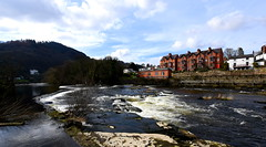 Llangollen (Peter.S.Roberts) Tags: llangollen riverdee northwales river water rapids whitewater town houses wier waves ripples blue rocks stones trees mountain dee bushes clouds afon afondyfrdwy spring afternoon march2018 redbrick dwellings walls sunshine reflections shadows sun sunlight riverside riverbank forest woodland forestry grass grasses colours colors colourful railway llangollenrailway platform riverview perspective pov dof properties peterroberts flickr nikon wideangle sigma peaceful quiet relaxing riverscene scenic wild riverwild explore flickriver interestingness photographyvision fotografíavisión