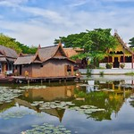 Lake with replica of traditional Thai village in Muang Boran open air museum in Samut Phrakan, Thailand thumbnail