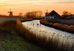 Dutch scating at sunset (Julysha) Tags: nikkor247028 cnx2 2009 january winter frost mills ice skaiting thenetherlands noordholland dutch schermer schaatsen d200 schermerhorn canal sunset